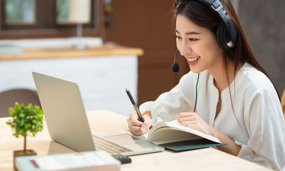 Smiling,Asian,Young,Female,Using,Headset,Looking,At,Laptop,Screen
